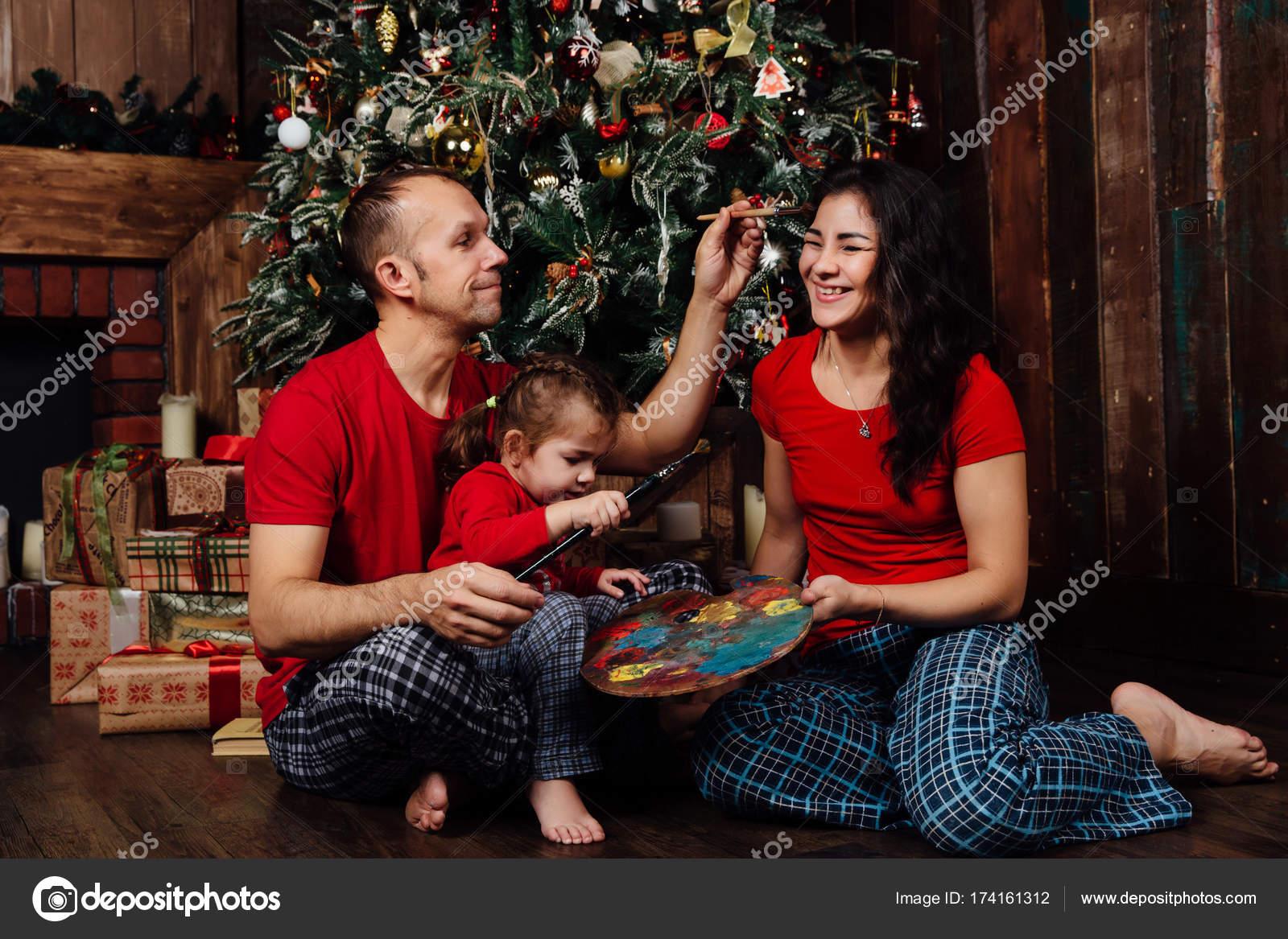 796608dca0f558 A família de pijama joga ao lado de uma árvore de Natal e uma ...
