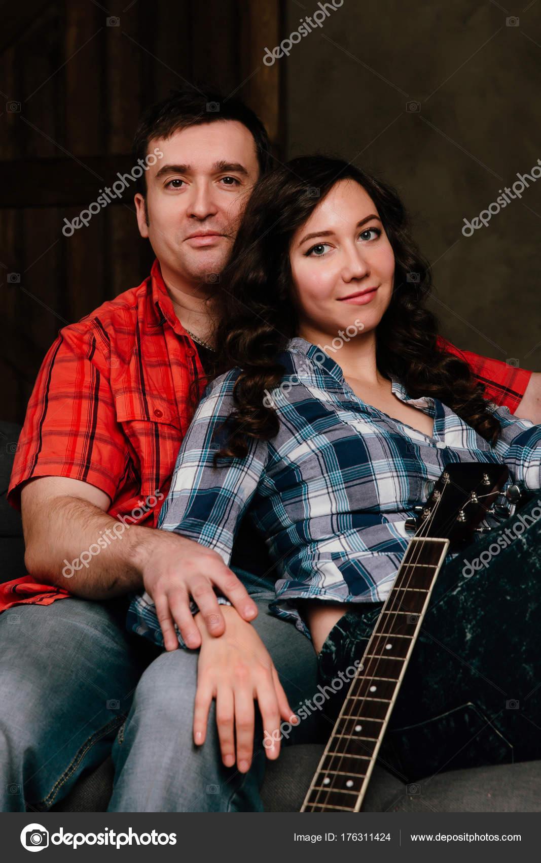 pareja está sentada en el sofá con una guitarra. Cabello largo de ...
