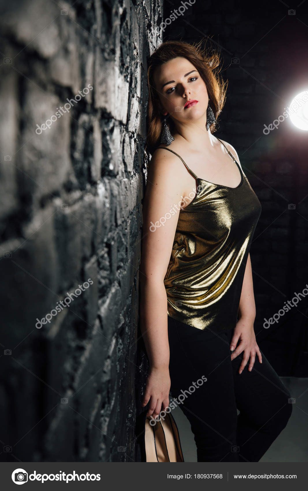 c408059322c2f Plus size model in a gold blouse and black jeans on a brick loft background.