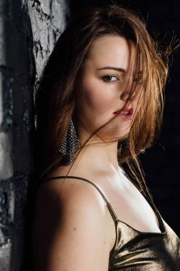 close-up portrait plus size model in a gold blouse and black jeans leaned on a brick loft wall.