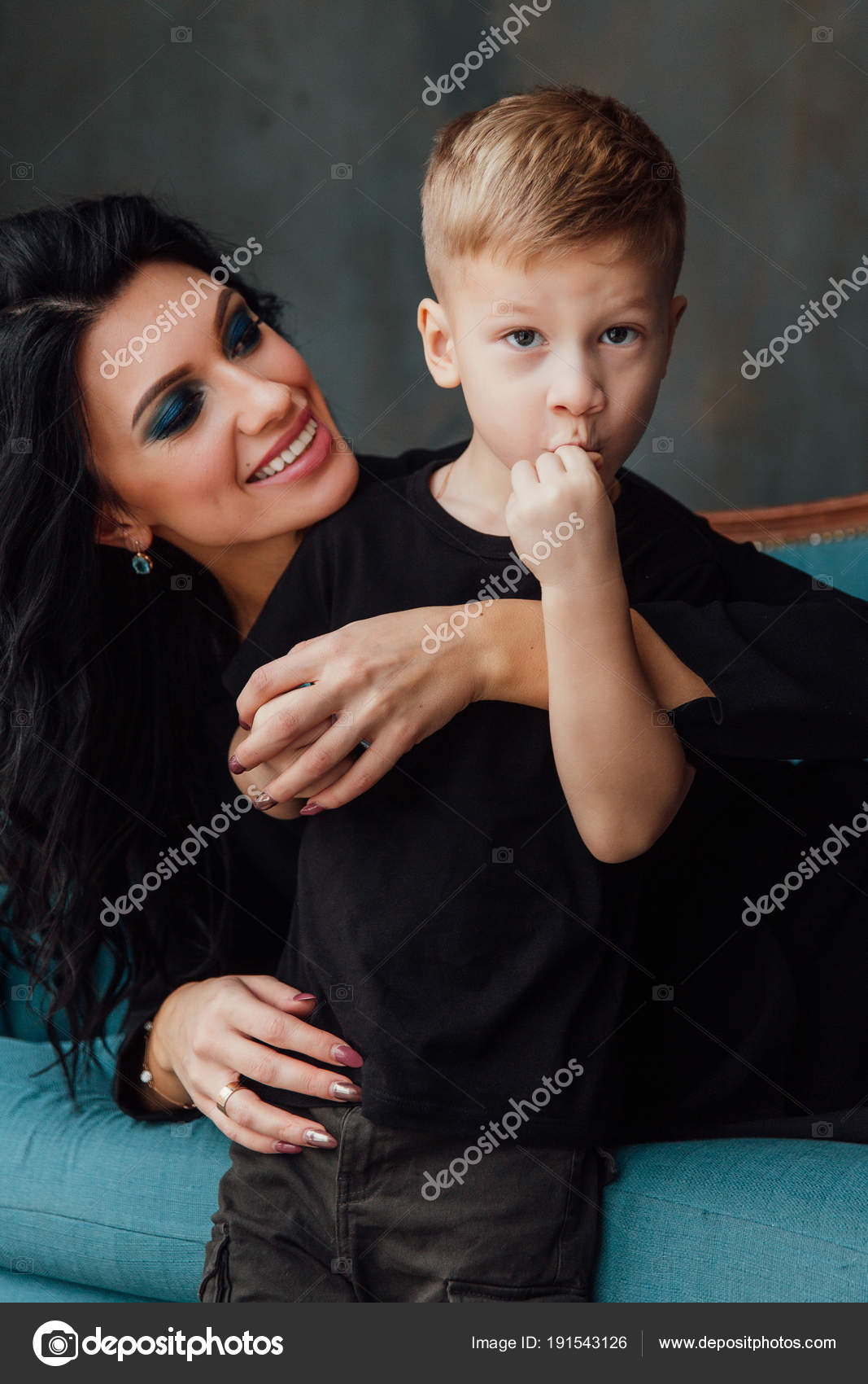 Beautiful Brunette Mom Hugging Her Son Lying On The Sofa Family Mother And Her