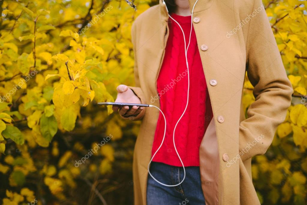 Hipster girl texting message on smartphone mobile in autumn natu