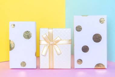 White gift box with a bow on a colorful pastel background. New year and birthday concept.
