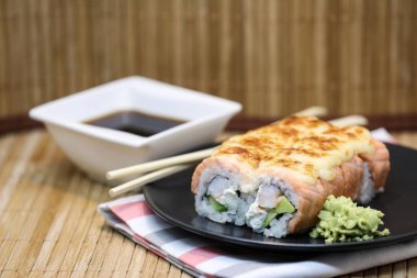 Sushi roll set on a plate, with sushi sticks on wooden background.
