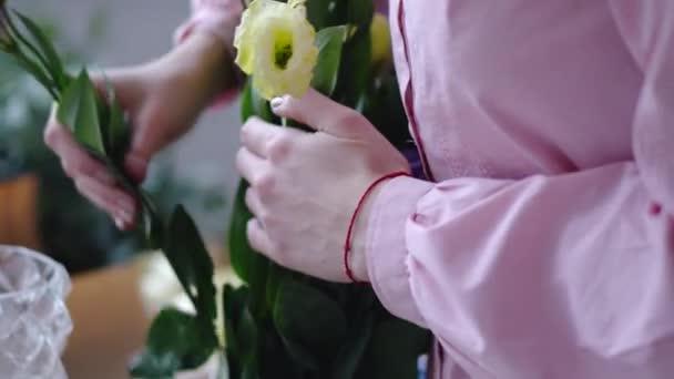 Mladá žena, pracující s žluté a fialové květy. Closeup
