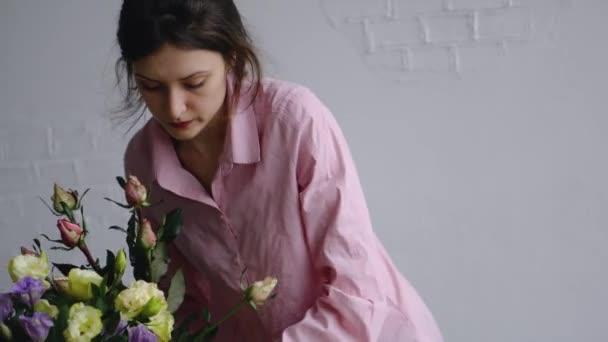 Dívka uspořádá vázu s květinami a připravuje balicí papír kraft kytice
