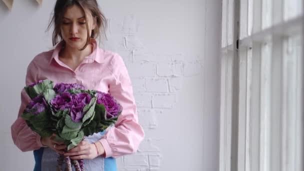Květinářství dívka vybere nejlepší květiny vytvořit kytici - okrasné zelí