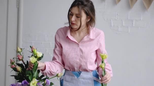 Egy fiatal virágkötő felveszi a virágok eustoma, és ellenőrzi őket a megállapodás