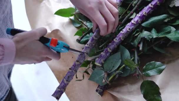 Florist cuts off excess big branch of exotic flower with a pruner