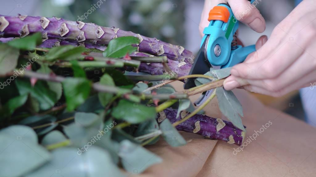 Female florist cutting excessive branches of bouquet