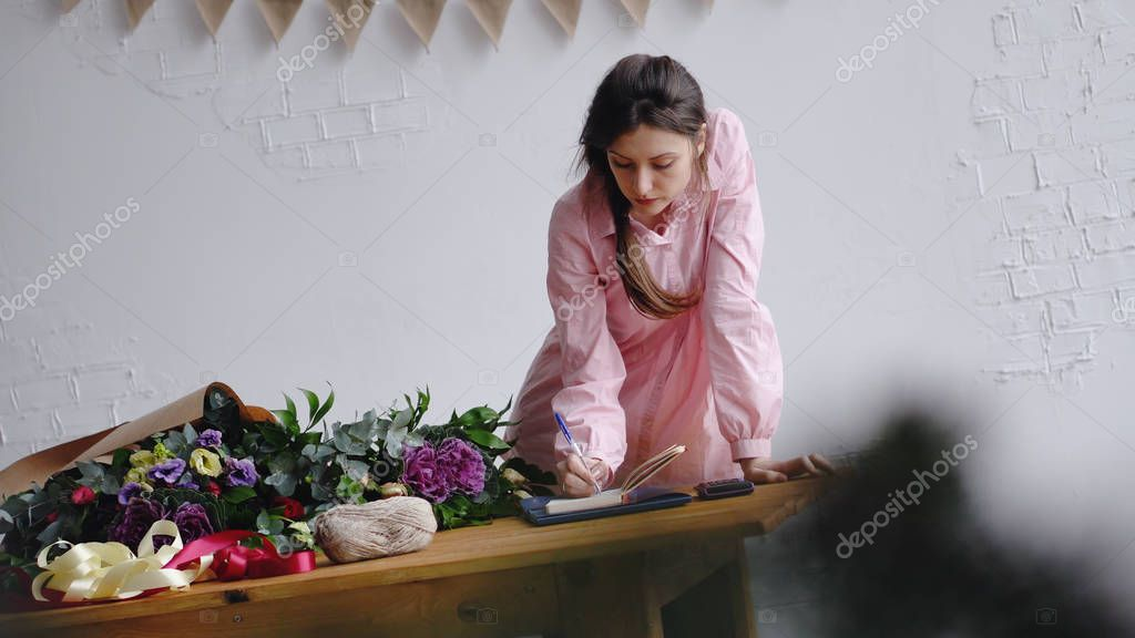 Florist girl writes notes in a notebook behind the counter