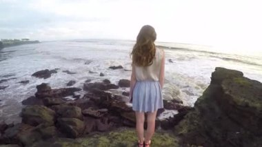 Shapely and tall girl stands on a rock on the coast of the ocean on the island Bali