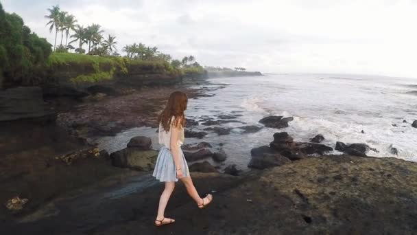 Girl walks along the rocks on the breathtaking coast at sunset, Bali in slow motion