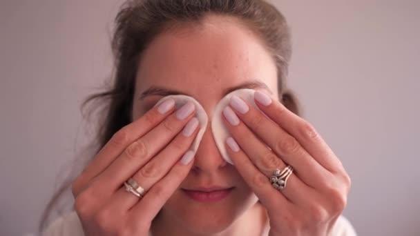 Aranyos fiatal nő tiszta arc bőr eltávolítja a sminket a szemek pamut párna. Sminktisztító. Kozmetikai bőrápolás