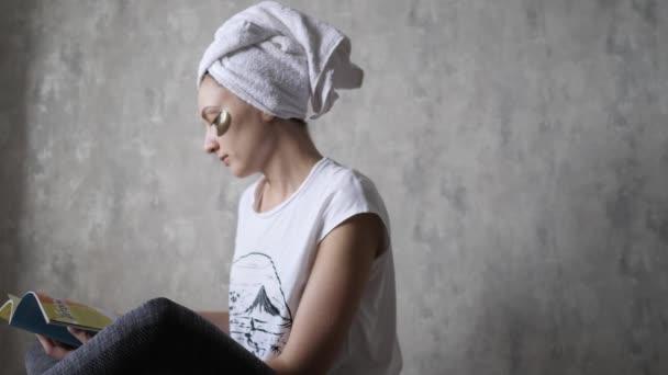 Entspannung zu Hause - eine junge Frau in Handtuch und mit Augenklappen liest eine Zeitschrift. Wellness-Lifting, Schönheitsbehandlungen