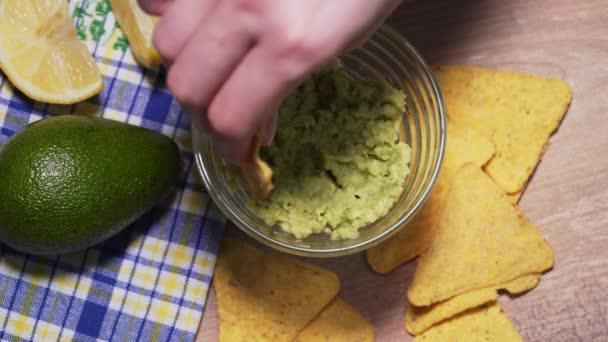 Rodina jí tradiční mexickou guacamole omáčku s hranolkami, horní pohled. Veganská svačinka z nezdravých a zdravých potravin