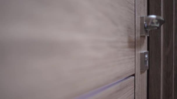 Žena zavře zámek na dveřích klíčem, zblízka. Ochrana domácnosti a bezpečnost