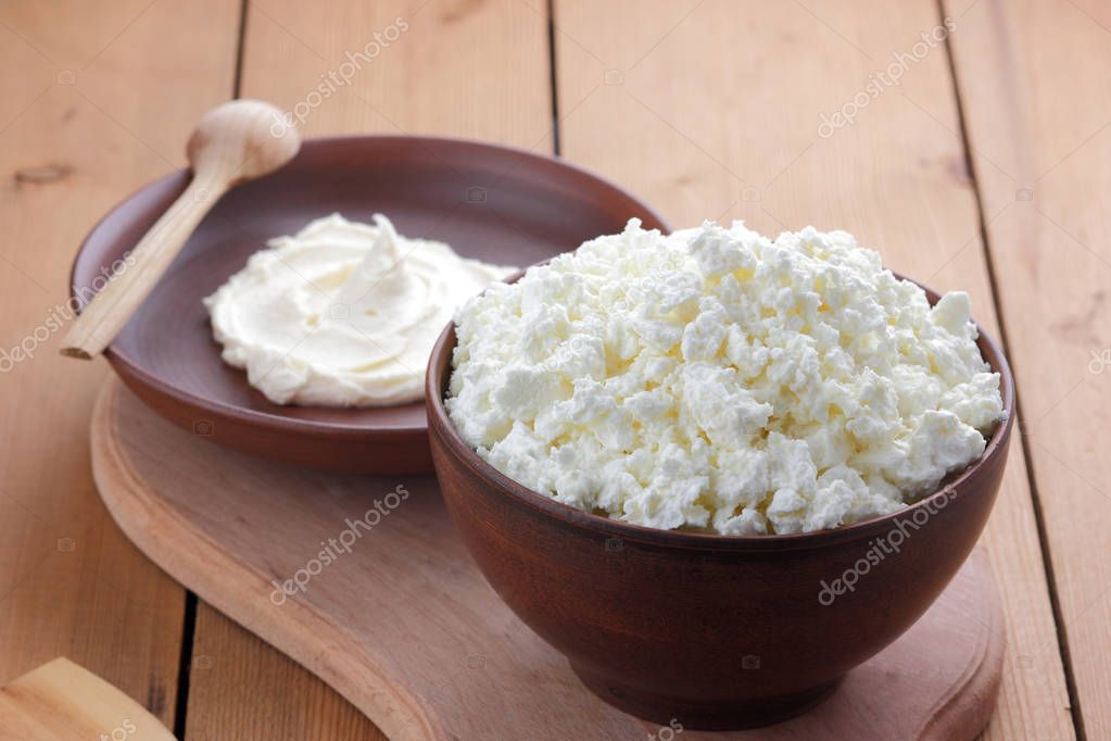 Cheese, cottage cheese and cream in clay ware, fresh curd on a wooden background, rustic sour cream, brown shade, healthy food, French breakfast, top view, goat curd, protein