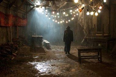 Man in black hat in the rain at dark overcast street
