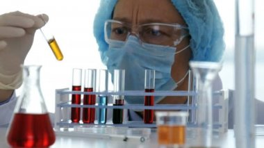 Lab technician controls chemical substances in test tubes