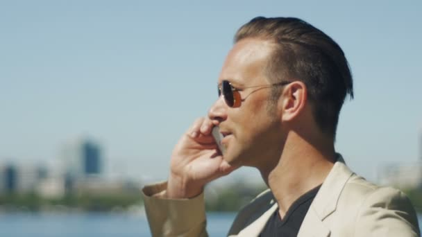 A Man In Sunglasses Talking To Someone Excited On The Phone Stock