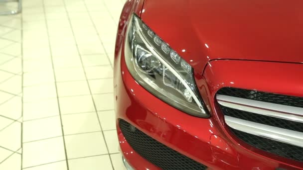 The front of the new red car. Headlight of the new machine. View of row new car at new car showroom.