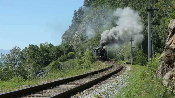 Historický parní vlak prochází pohoří. Parní lokomotivu, pohybující se po horách. Trans-sibiřská železnice, jezero Bajkal. Vintage železnice podél břehu jezera. Rusko Sibiř
