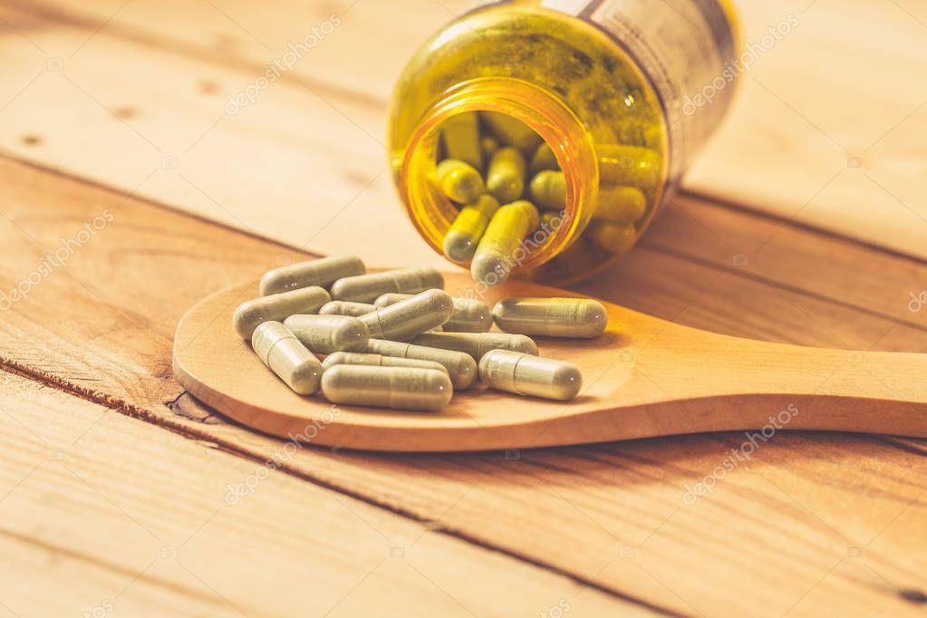 green herbal powder in capsule on wood background, Dried Kariyat for medicine.