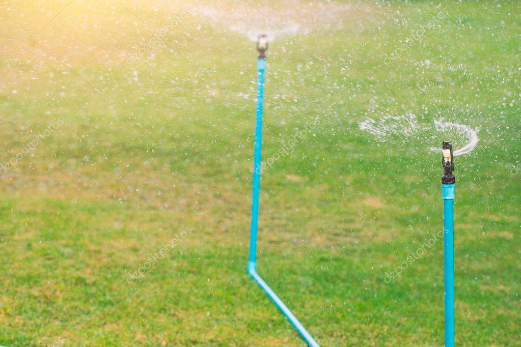 water spray sprinkler in grass field.