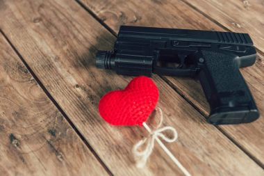 pistol gun and love red heart on wood background