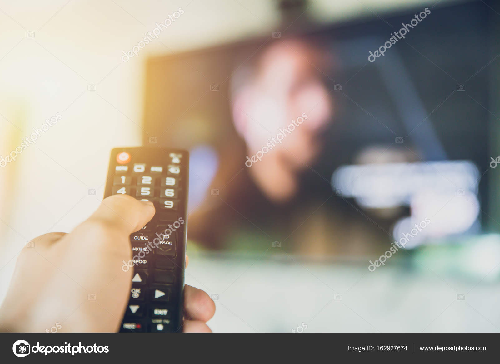 Hand hold Smart TV remote control with a television blur