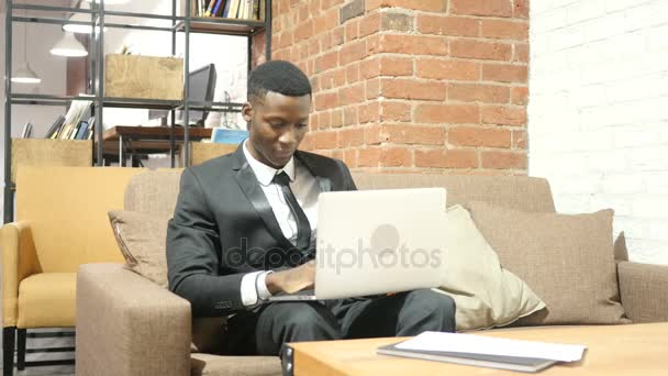 Black Businessman Cheering Success, Working on Laptop