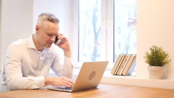 Telefonat eines Mannes mittleren Alters während der Arbeit am Laptop