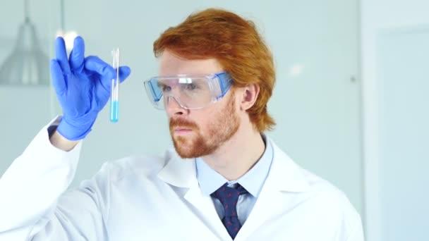 Vědecký pracovník, lékař při pohledu na modrou roztoku ve zkumavce v laboratoř