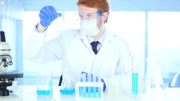 Výzkumník při pohledu na modrou roztoku ve zkumavce v laboratoři