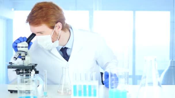 Tudós keresi kémcsőbe kék megoldás és használ Mikroszkóp-ban Laborato