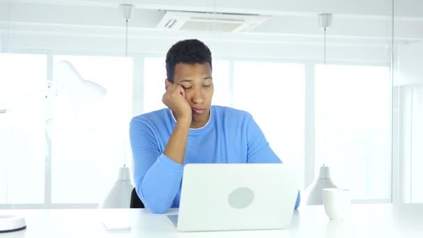 schlafender junger afroamerikanischer Mann sitzt bei der Arbeit