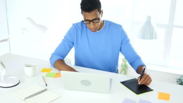 Afro-American kreativní návrhář pracující s grafikou tablet na notebook