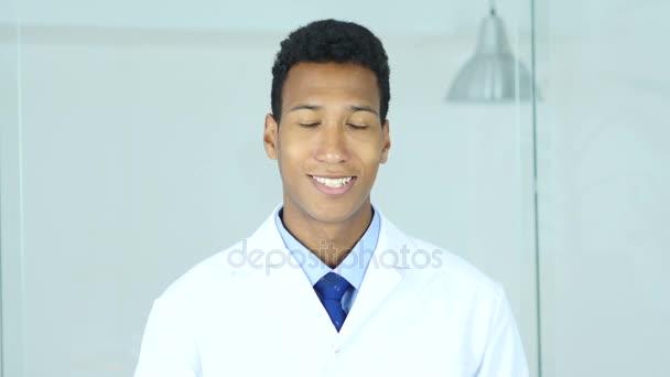 positiv lächelnd entspannen afroamerikanische Arzt sitzt in Klinik, Chirurg