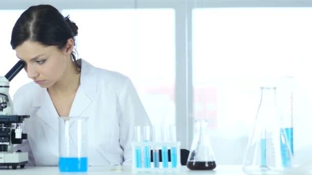 Chemik, vědecký Reseacher pracuje na mikroskopem v laboratoři