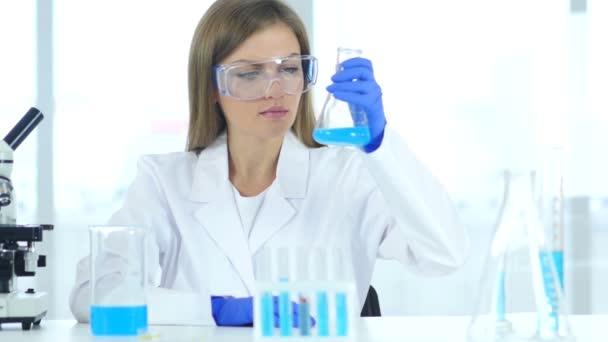 Female Research Scientist Looking at Blue Solution in Flask in Laboratory