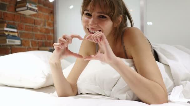Srdce znamení usmíváš pozitivní žena ležela v posteli