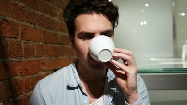 Portrét mladého muže pít kávu z poháru