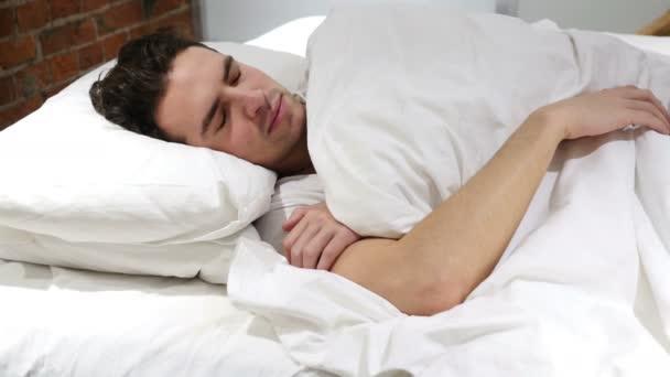 Mladý muž probuzení z režimu spánku v posteli, ráno