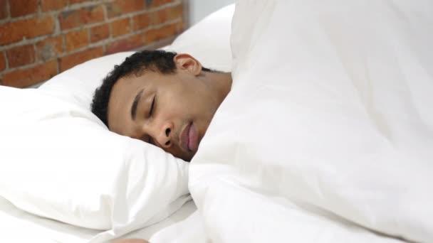 Afrikai férfi oldalán az ágyban alszik, éjszaka