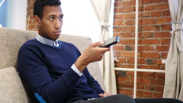 Africký muž sleduje a přepínání kanálů Tv s dálkovým ovládáním