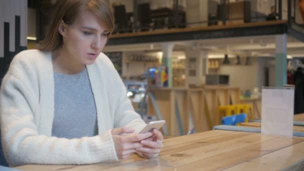 Nespokojený žena pomocí Smartphone v Cafe, rozrušený, problémy