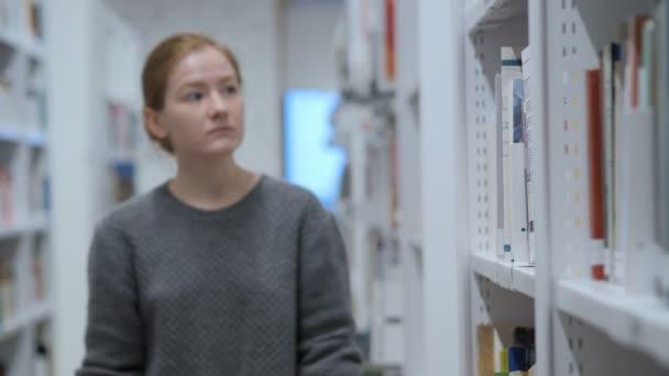 Studentka hledá knihu v knihovně
