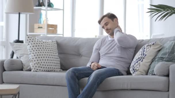 Müder erwachsener Mann mit Nackenschmerzen sitzt auf der Couch und versucht sich zu entspannen
