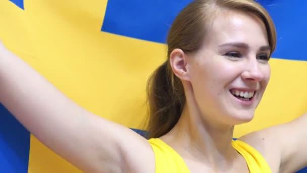Femme Suedoise jeune suédoise femme célèbre, tenant le drapeau de la suède en slow